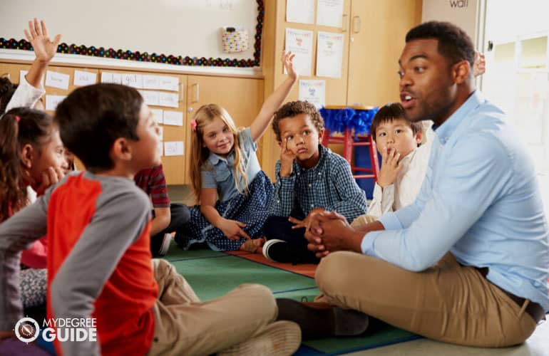 male teacher teaching elementary kids
