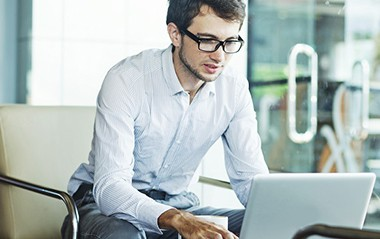 young guy looking for an easy online bachelor degree programs on laptop