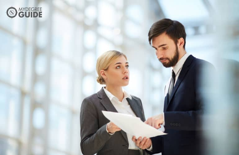 paralegal discussing some documents to a fellow paralegal