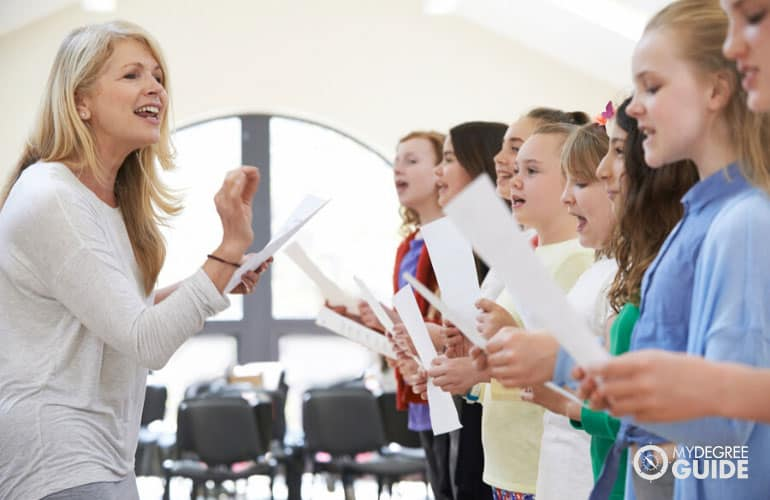music teacher teaching children in a classroom