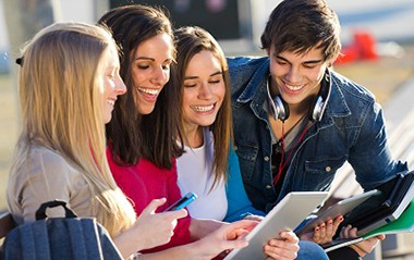 a group of students having fun with smartphones while looking for IT Bachelor Degree Programs