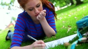 Student lying on the grass studying