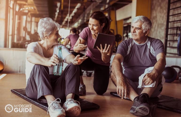 fitness trainer assisting a senior couple