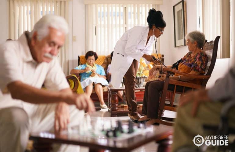female doctor checking seniors at a nursing home