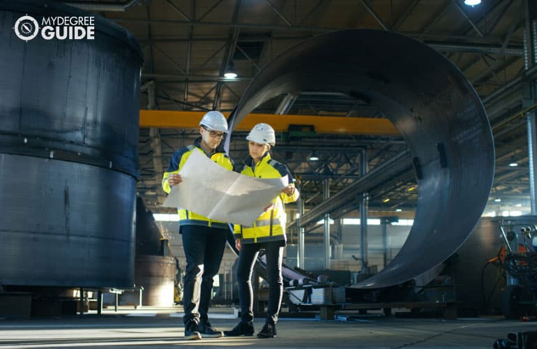 Industrial Engineers looking at a plan in a manufacturing factory