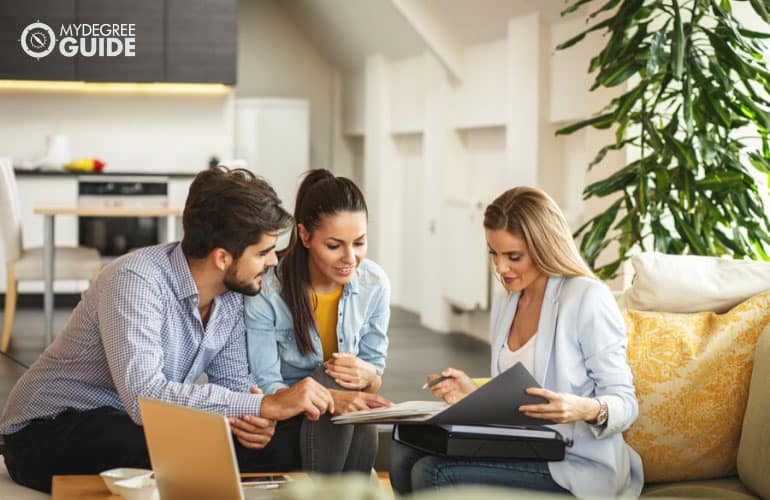 Real Estate broker closing a deal with a young couple