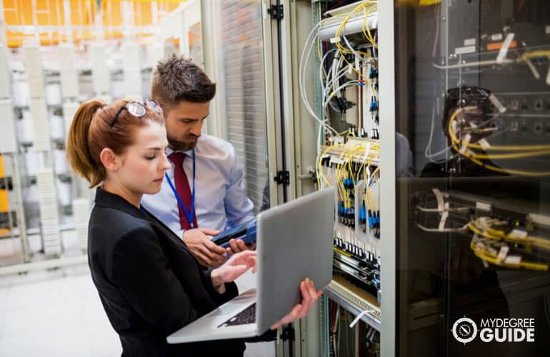 systems engineer using laptop to analyze server in server room