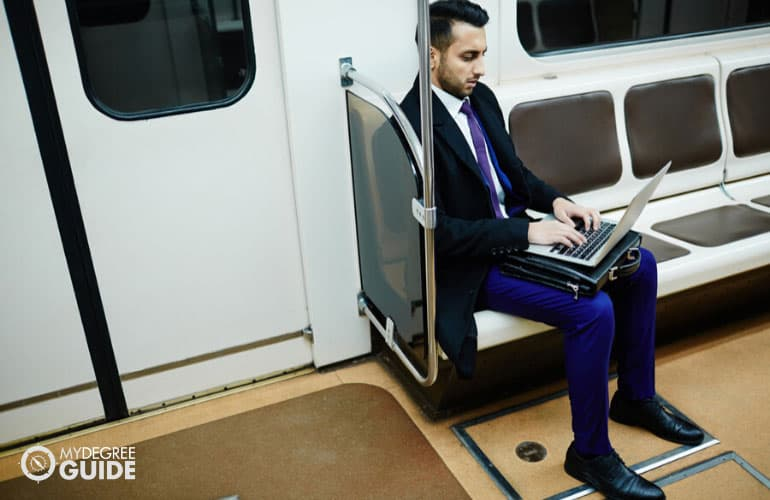 male professional working on his computer while commuting to work