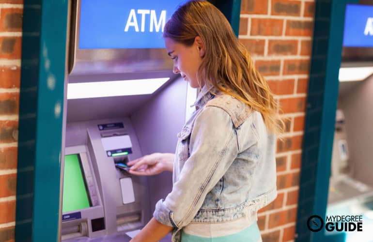 students withdrawing money at an atm machine
