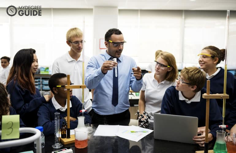 high school teacher doing science experiments with students