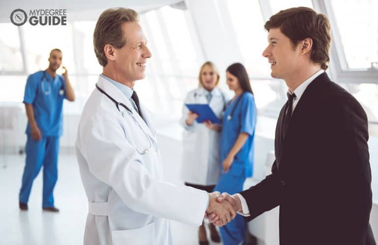 healthcare administrator shaking hands with a colleague