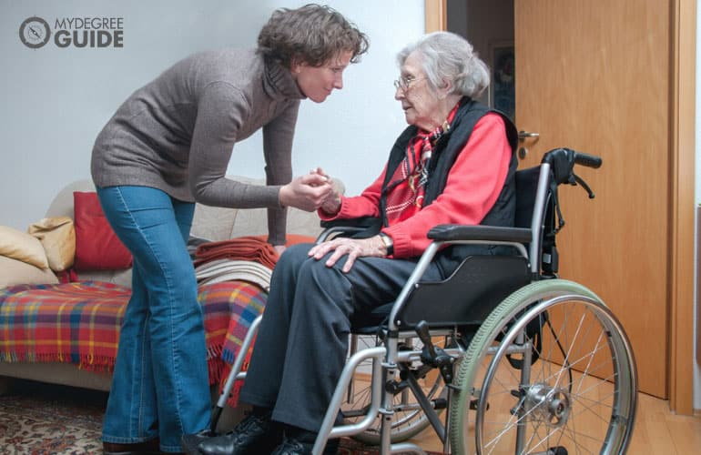 caregiver taking care of a senior woman on a wheelchair