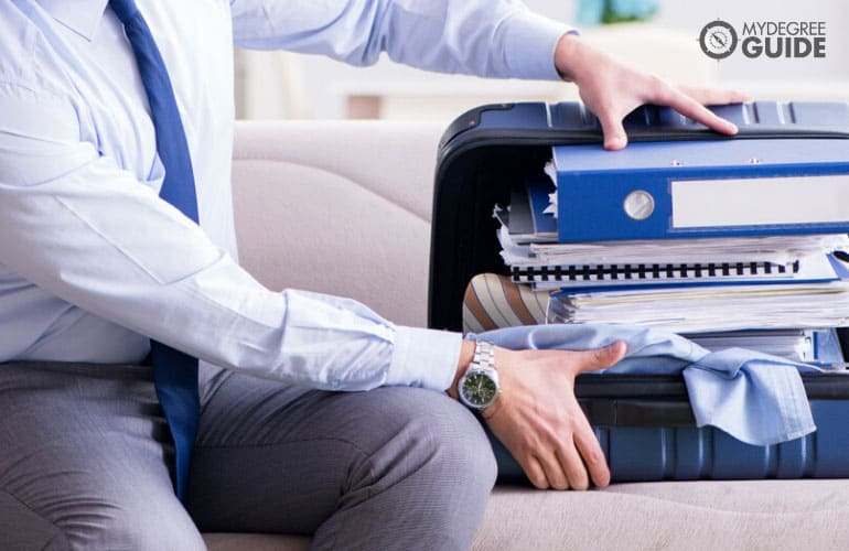 man trying to fit his things in his briefcase