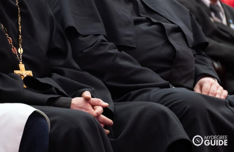 clergy and priests sitting in a church