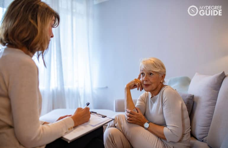 female psychiatrist interviewing a senior woman during therapy session