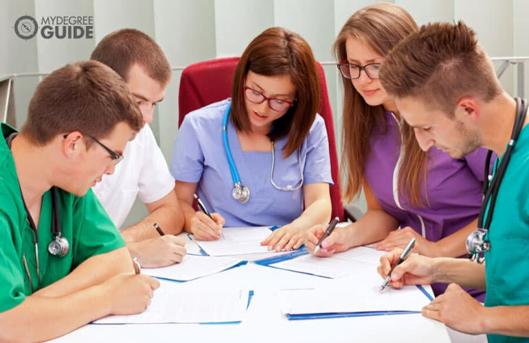 healthcare professionals filling documents during a meeting