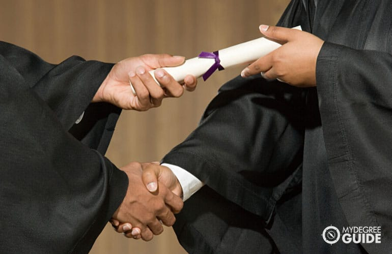 a person receiving a diploma at a graduation ceremony