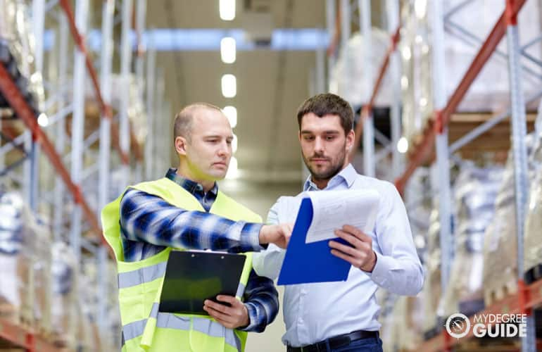 logistics manager talking to an employee in a warehouse