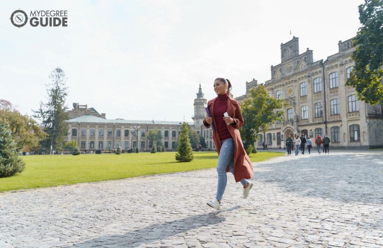 a student running across campus