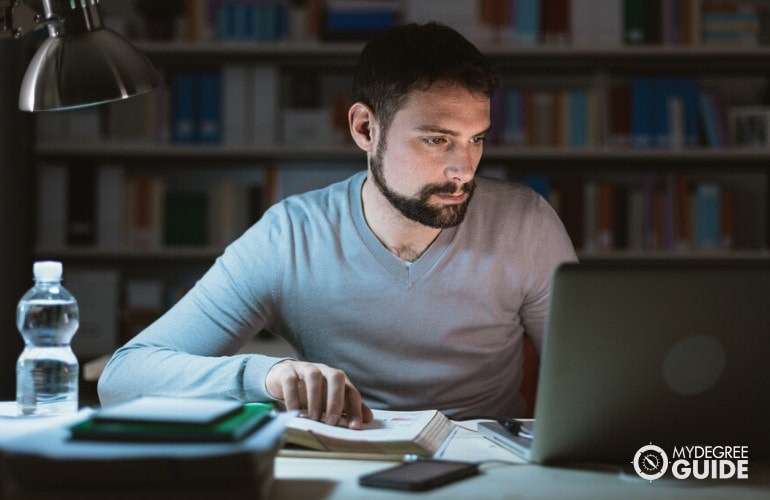 theology degree student studying on his computer at home