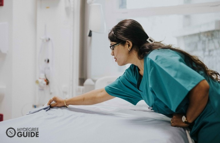 nurse fixing a patient's bed