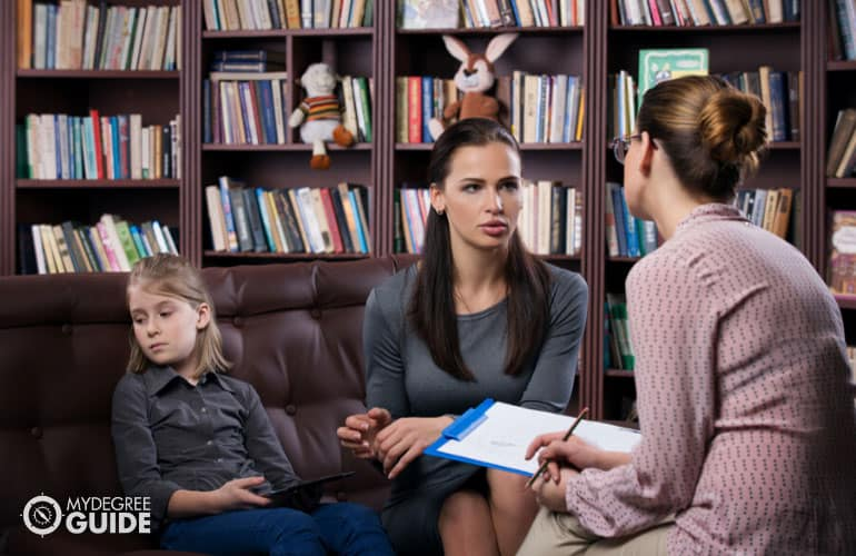 female guidance counselor talking to a parent and child