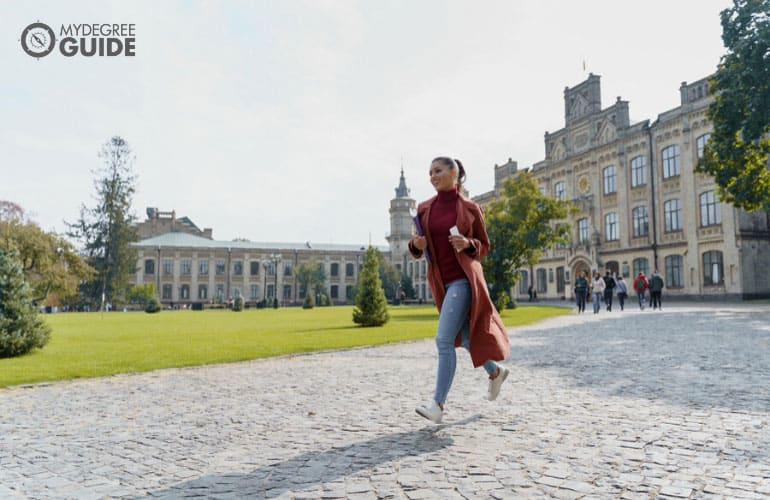 hospitality management student running across campus