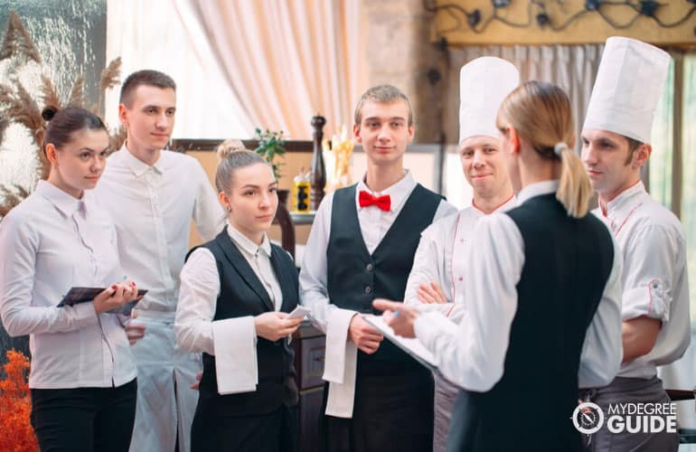 restaurant manager discussing with her staff in a commercial kitchen