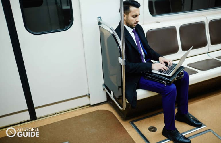 a commuter in professional wear working on his laptop