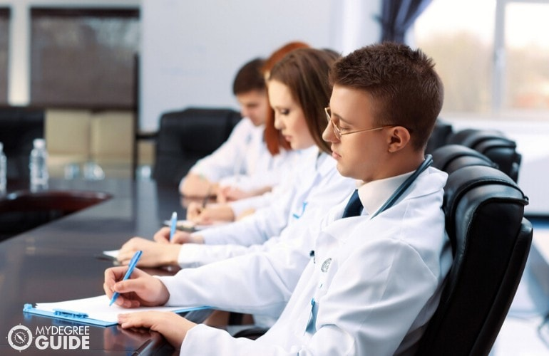 healthcare administrators taking notes during a meeting
