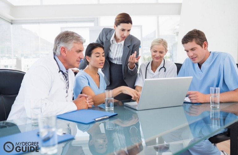 healthcare administrator discussing to medical doctors during a meeting