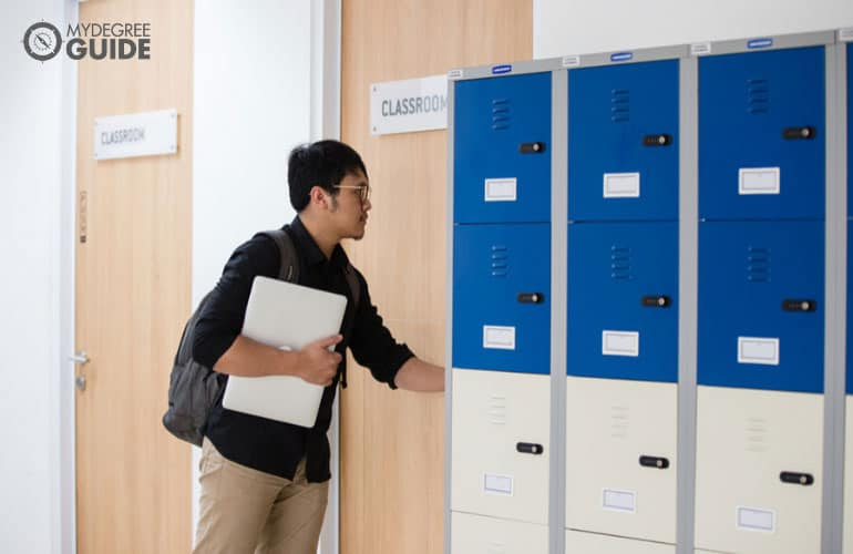 male student walking into a classroom