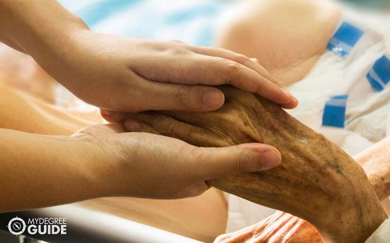 holding hand of old patient