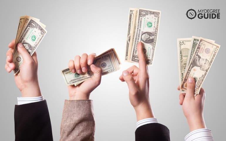 PhD graduates holding dollar bills
