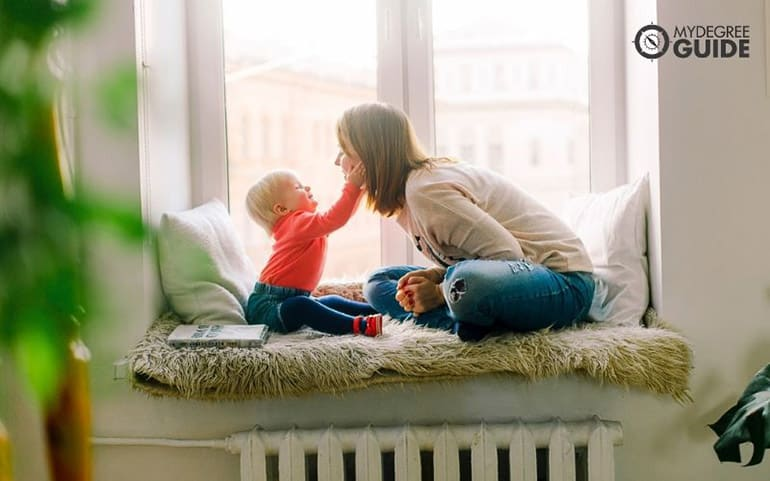 mother and son playing near window