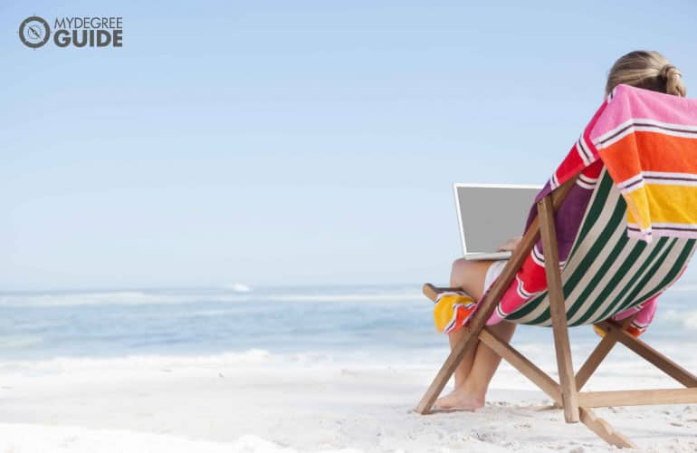 female sitting on a beach looking at their laptop