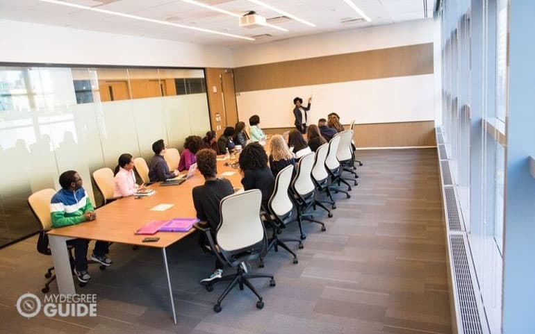 meeting in conference room lead by a doctorate of education graduate