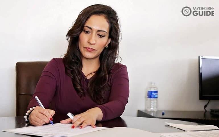 education executive sitting at desk writing notes