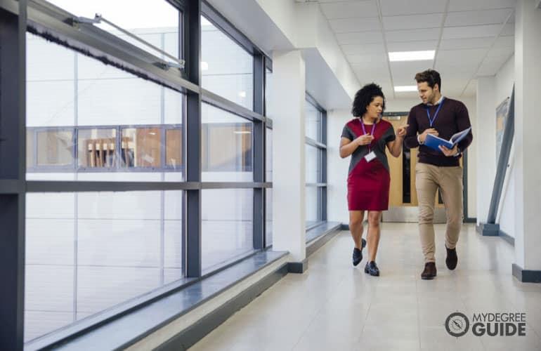 two educators walking in a university hallway