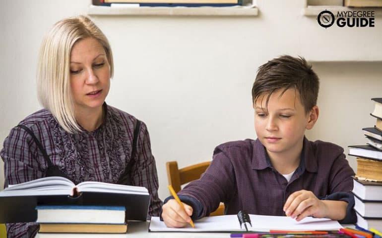 K-12 teaching young boy in classroom