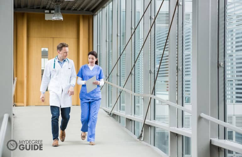 doctor and nurse talking while walking on the hospital hallway