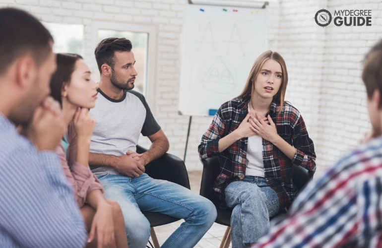 female sharing her problems during group therapy session
