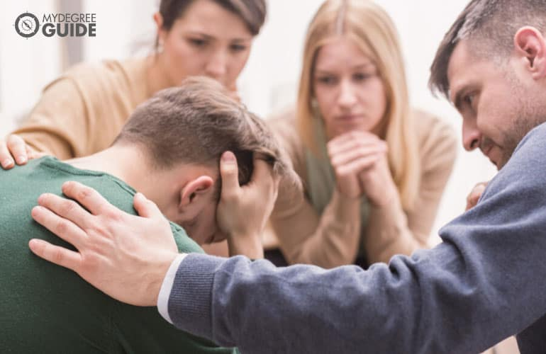 devastated young man and his friends supporting him during group therapy