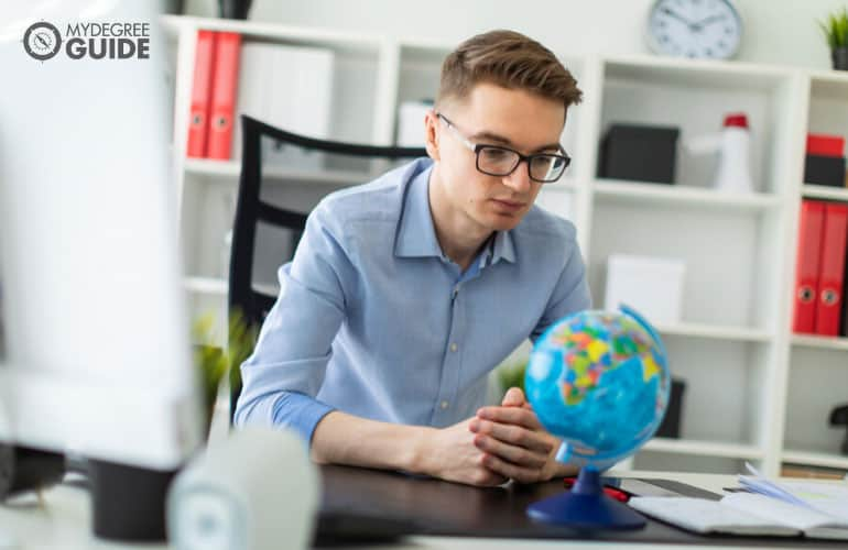 person looking at a globe