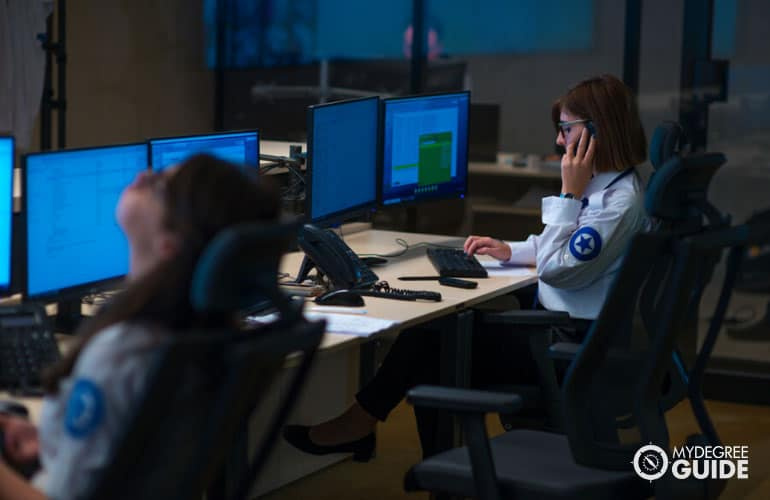 security personnel monitoring CCTV cameras in surveillance room
