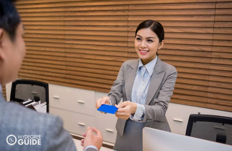 female hotel receptionist handing key card to guest