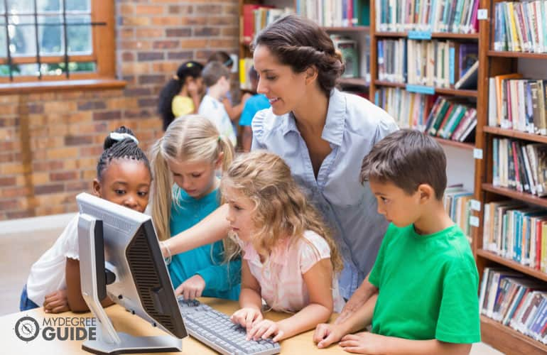 librarian teaching kids how to use computer