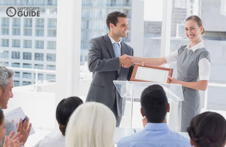 MBA in Finance graduate receiving her certificate