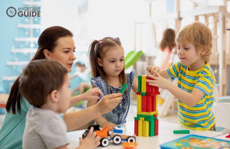 preschool teacher assisting the kids during playtime