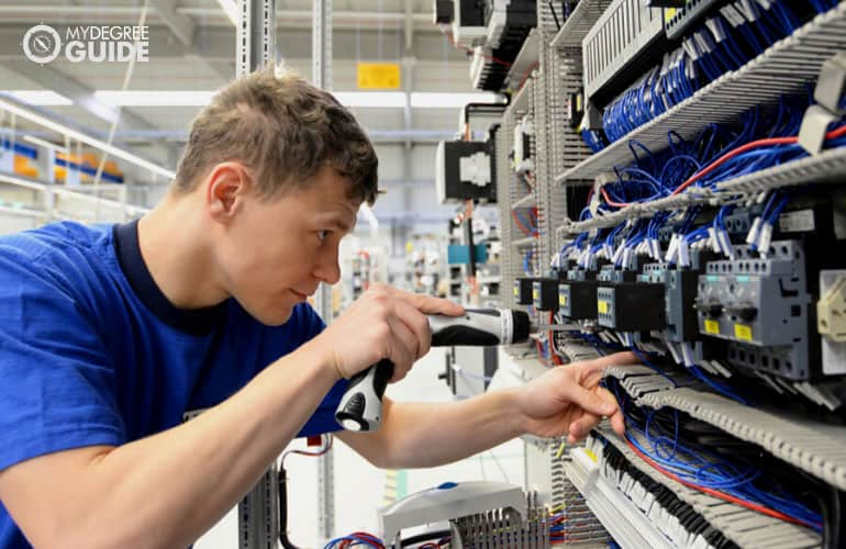 electrical engineer fixes cables in a modern factory